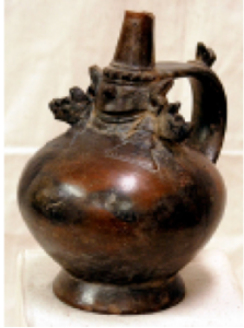 "One of my favorite pieces from the exhibition – a stirrup spout vessel representing Naylamp. Naylamp was the mythological ""first ruler"" of the Sicán culture who sailed from the south on balsa rafts and colonized many valleys in the region of what is today Peru. When he died, he sprouted wings and flew away to another world."