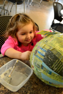 A young volunteer helping to create paper mache balloons for Whisper, our Bobcat.